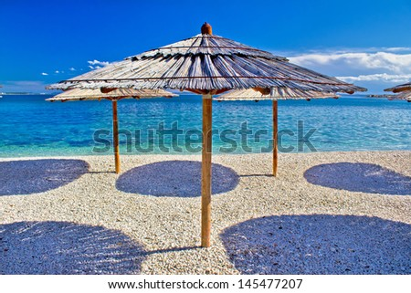 Pebble beach and turquoise sea umbrella, Zrce beach, Island of Pag, Croatia - stock photo