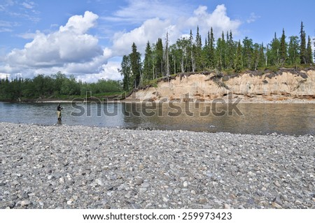 Pebble beach North of the river and fisherman. Summer landscape of one of the rivers of the Northern slope of the Polar Urals. - stock photo