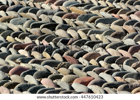 Pebble pavement pattern closeup. Stone mosaic background. Focus is in the middle - stock photo