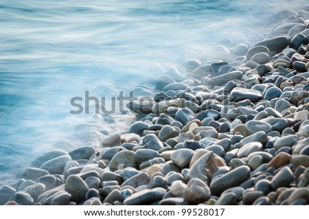 pebble stones by the sea. Silky waves of blue sea from long exposure. - stock photo