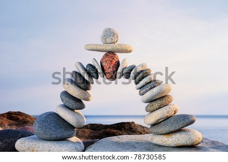 Pebbles curved as arch on the seashore - stock photo