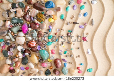 Pebbles, gemstones and shells scattered in a decorative arrangement on tropical golden beach sand with a ridged undulating wavy pattern in an ornamental nautical background - stock photo