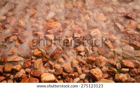Pebbles on beach against waves (Daylight long exposure) - stock photo