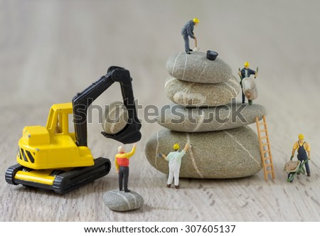 Pebbles stack and figurines of construction workers - stock photo