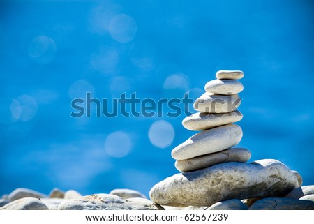 Pebbles stack balance over blue Adriatic sea in Croatia. Blue sky and water on sunny coast in summer. - stock photo
