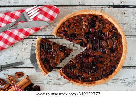 Pecan and cranberry autumn pie, overhead table scene on white wood with slice being removed - stock photo