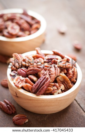 Pecan nuts in wooden bowel on wooden background with copy space for text - stock photo
