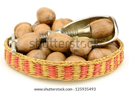 Pecans and a nut cracker in the studio,  Good source of essential nutrients. - stock photo
