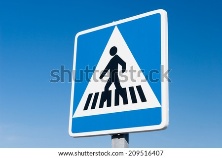 Pedestrian blue road sign against blue sky - stock photo