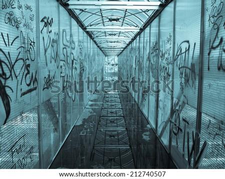 Pedestrian bridge with graffiti picture - cool cyanotype - stock photo