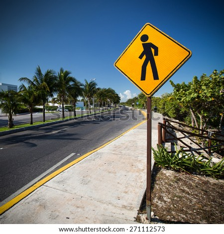 Pedestrian crossing sign on tropical street  - stock photo