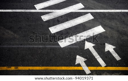 Pedestrian crossing with road marking: white arrows and rectangles on the dark asphalt road - stock photo
