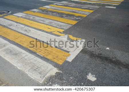 Pedestrian crossing with the old road markings on a dark asphalt - stock photo