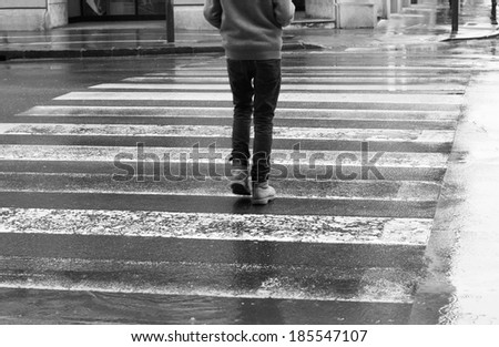 Pedestrian crosswalk on a rainy day, walking in the city in rain. Black and white - stock photo