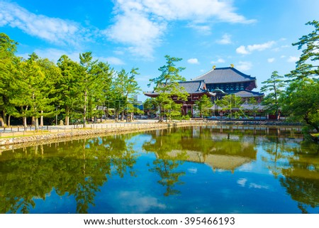 Pedestrian path and tranquil lake reflecting the front red entrance gate to Daibutsuden seen in distance on beautiful, sunny blue sky morning at Todai-ji temple in Nara, Japan. Horizontal copy space - stock photo