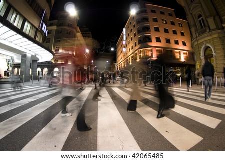 Pedestrian zebra crossing on busy street at night - stock photo
