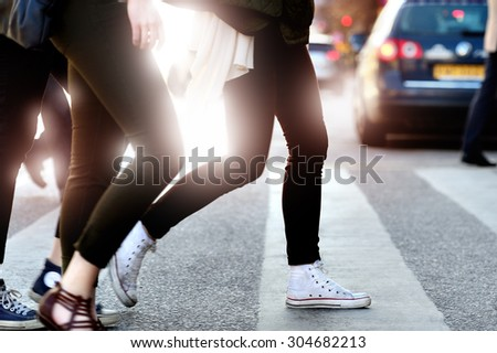Pedestrians crossing street against bright light - stock photo