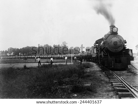 Pedestrians waiting at a railroad crossing for Louisiana Arkansas Railroad train pulling tank cars to pass. Ca. 1920-1940. LC-USZ62-106094 - stock photo