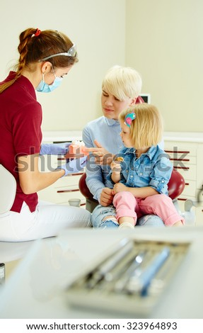 Pediatric dentist explaining to young patient and her mother the model in dental clinic - stock photo