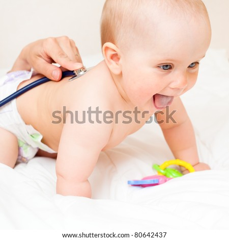 Pediatric doctor exams little baby girl with stethoscope - stock photo