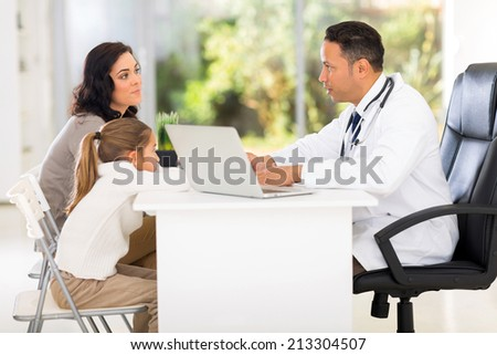 pediatric doctor talking to patient's mother  - stock photo