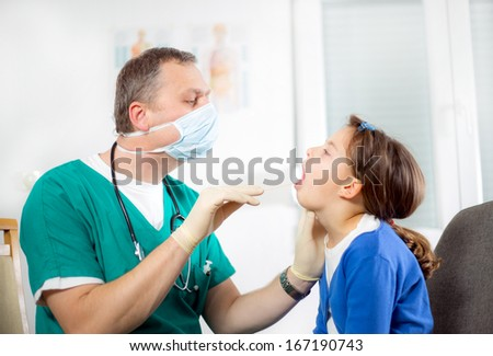 Pediatrician checking little girl throat - stock photo