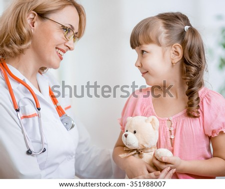 Pediatrician doctor talking with kid - stock photo