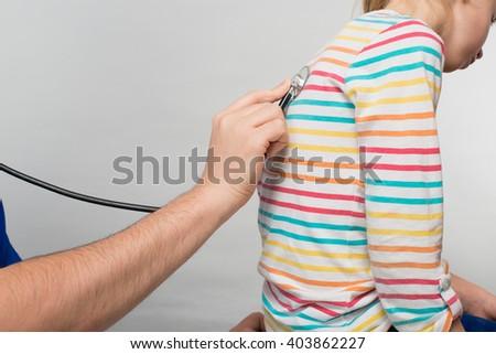 pediatrician examines a child - stock photo