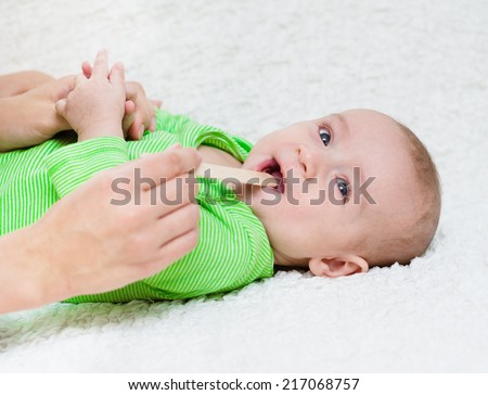 pediatrician  examines a newborn baby with a spatula - stock photo