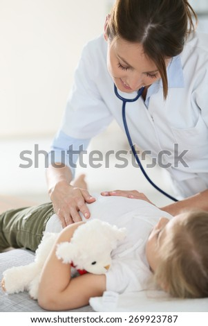 Pediatrician examining child's stomach - stock photo