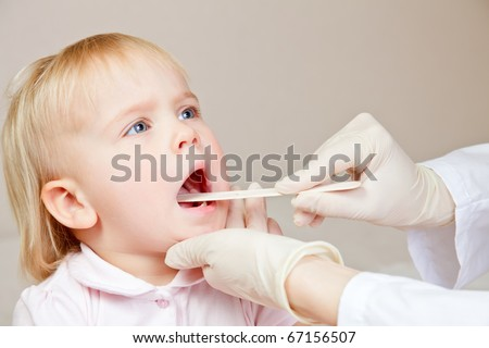 Pediatrician examining little girl's throat with tongue depressor - stock photo