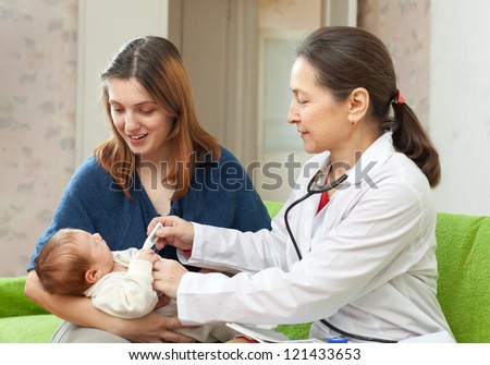 pediatrician  examining newborn baby with thermometer. Focus on mother - stock photo