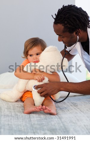 Pediatrician exams a little girl with stethoscope in a hospital - stock photo