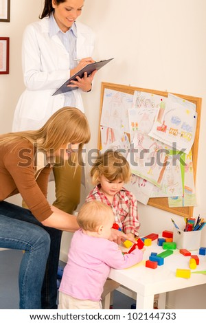 Pediatrician female observe children playing activity fill medical report - stock photo