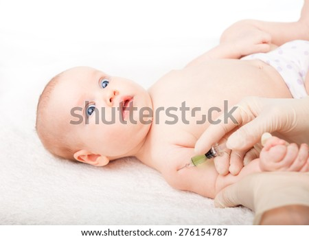 Pediatrician giving a three month baby girl  intramuscular injection in arm. Child looking anxiously at a doctor - stock photo