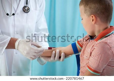 Pediatrician taking blood sample of 4 years old boy - stock photo