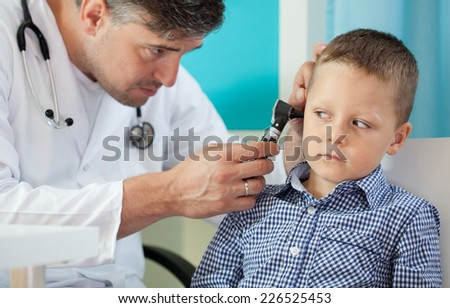 Pediatrician using otoscope to examine boy's ear - stock photo