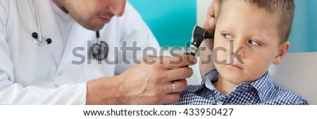Pediatrician using otoscope to examine boy's ear - stock photo