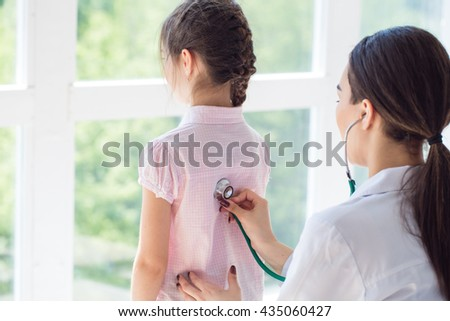 Pediatrician with child in doctor's office - stock photo