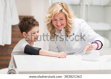 Pediatrician with little boy, checking blood pressure, having fun - stock photo