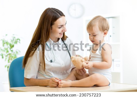 pediatrician woman with kid playing with stethoscope - stock photo