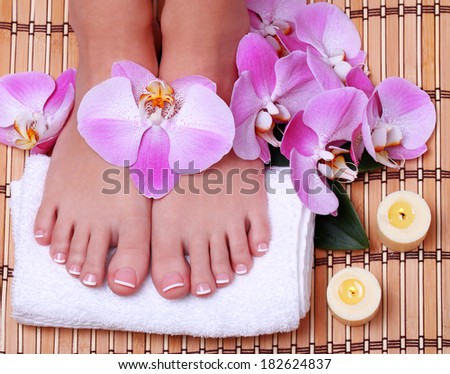 Pedicure. Beautiful female feet with french manicure and pink orchid flowers on bamboo mat.  Foot care. Spa Salon - stock photo