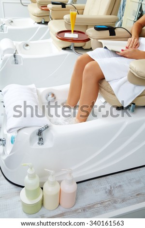 Pedicure feet bath in sofa chair woman at nails salon - stock photo