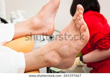pedicure male feet in a modern beauty salon - stock photo