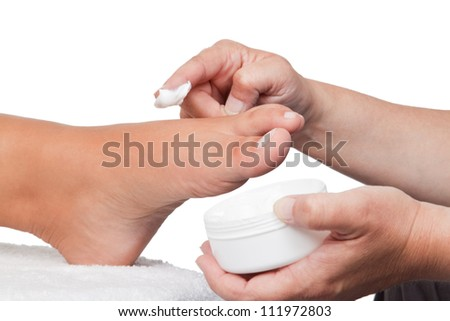 Pedicurist putting some cream on a foot - stock photo