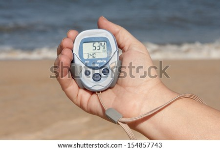 Pedometer In A Hand On The Beach - stock photo