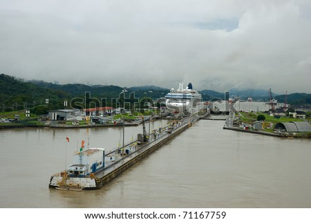Pedro Miguel locks. Panama city buildings can be seen behind the hills in the background as well as the Miraflores locks. - stock photo