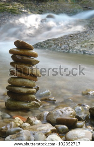 peebles in balance in front of a water fall - stock photo