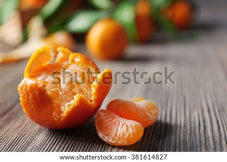 Peeled fresh tangerine with leaves and ripe mandarins on wooden table, closeup - stock photo