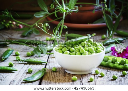 Peeled pea green peas in a white porcelain bowl, vintage wooden background, selective focus - stock photo